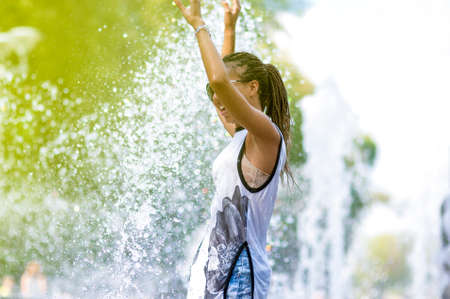 Portrait of Smiling Funny African American Teenager Girl with Dreadlocks Enjoying in Fountain Outdoors Stock Photo
