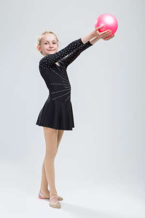 Full Length Portrait of Caucasian Female Rhythmic Gymnast In Professional Competitive Black Suit Posing With Ball in Studio On White. Vertical Image Composition
