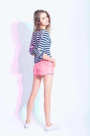 Youth Lifestyle Concepts and Ideas. Portrait of Caucasian Brunette Girl in Striped Shirt and Sexy Shorts. Standing Half Turned Backwards Against White. Vertical Image