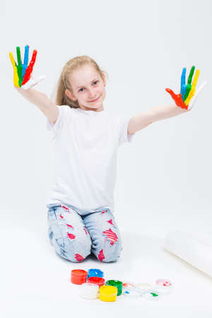 Kids Concepts and Ideas. Portrait of Funny Young Girl Showing Messy Colorful Hands Brightly Painted During Paint Craft. Against White Background.Vertical Image Orientation