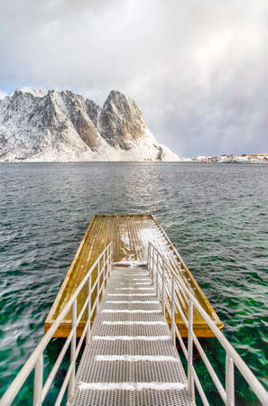 Travel Destinations. Unique Floating Bridge on Water In Traditional Sakrisoy Village in Northern part of Norway. Against Snowy Mountain Peaks.Vertical Composition Stock Photo