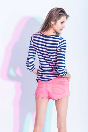 Portrait of Smiling Caucasian Brunette Girl in Striped Shirt and Pink Shorts. Standing Half Turned Backwards Against White. Vertical Image
