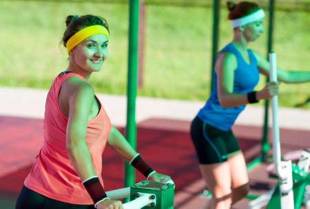 Sport Ideas and Concepts. Two Active Caucasian Females In Good Fit Doing Outdoor Workout. One Athlete Looking Straight To Viewer. Horizontal Image