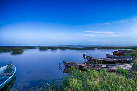 Scenic Destinations. Line of Boats on Water Placed in Belarussian National Park Braslav Lakes at Sunset during Summer Time. Horizontal Image Orientation Stock Photo
