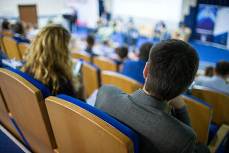Business and Entrepreneurship Ideas. Speaker On Stage Giving a Talk at Business Meeting or Conference. Back View of the Listeners.Horizontal Image Stock Photo