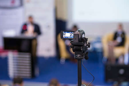Back View of Compact Videocamera. Positioned Against Blurred Background with Host Speaking on stage. Horizontal Image Stock Photo
