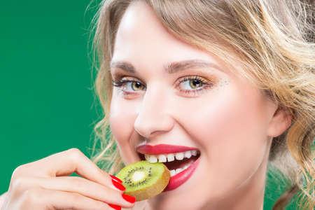 Fruit Kiwi Series. Closeup of Sensual and Sexy Naked Caucasian Model with Teeth Diastema Posing With Juicy Kiwi Fruit. Against Green. Horizontal Shot