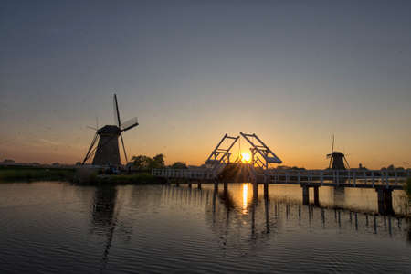 Travelling Concepts and Ideas. UNESCO Heritage Dutch Windmills and Old Bridge at Kinderdijk Located in Traditional Village in Holland, The Netherlands. Plenty of Insects in The Air. Horizontal Image Stock Photo