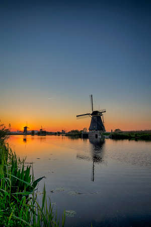 Travelling Concepts and Ideas. UNESCO Heritage Dutch Windmills In Front of The Canal and Sun at Kinderdijk Located in Traditional Village in Holland, The Netherlands. Vertical Image Stock Photo