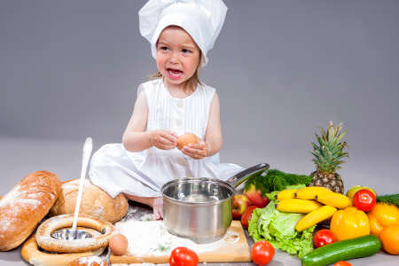 Coocking Ideas and Concepts. Portrait of Surprised Caucasian Little Girl In Cook Uniform With Fresh Eggs and Saucepan In Studio with Vegetables At Background. Posing with Angry Expression. Against Gray. Horizontal Image