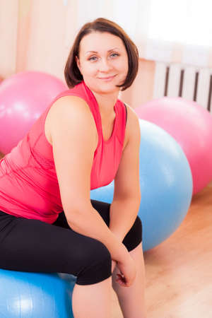 Sport, Fitness, Wellness and Lifestyle Ideas.Portrait of Female Caucasian Athlete In Good Fit Sitting on Big Fitballs in Gym and Smiling. Vertical Image Composition