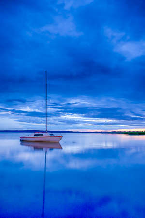 Picturesque Image of Braslav Lakes in Belarus At Sunset Time. Small Sailing Boat on The Background. Taken During Blue Hour. Vertical Image Orientation