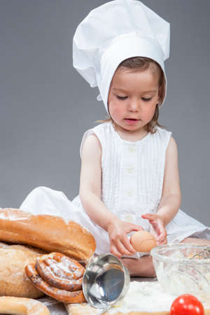 Caucasian Girl In Specific Cook Uniform Breaking Down Fresh Egg and Making Food in Kitchen Glassware with Whisk In Studio Environment. Against Gray Background. Vertical Shot Stock Photo