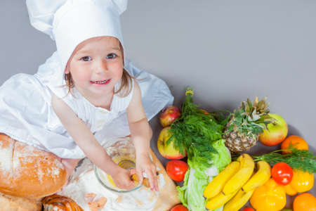 Cooking Ideas. Caucasian Little Girl In Cook Uniform Working With Whisk and Kitchen Glassware In Studio Environment. With Vegetables and Fruits on Background.High Angle View. Horizontal Image