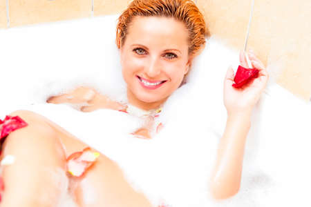 Wellness and Beauty Concepts. Smiling Sexy Caucasian Woman Relaxing in Bath with Petals During Skin Treatment. Horizontal Image Composition