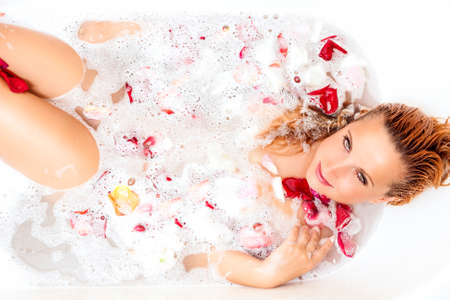 Wellness, Spa and Beauty Concepts and Ideas. Alluring Sexy Caucasian Ginger Woman Relaxing in Foamy Bathtub Filled With Flowers Petals.Horizontal Image