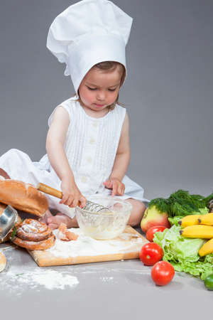 Cooking Concepts. Caucasian Girl In Cook Uniform Working With Kitchen Glassware with Whisk In Studio Environment. With Vegetables and Fruits on Background. Vertical Shot
