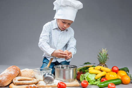 Cuisine Concepts. Portrait of Fascinated Caucasian Little Boy Crashing Fresh Egg In Cooking Hat. Surrounded by Fresh Fruits and Vegetables In Studio. Posing with Smiling Expression. Against Gray. Horizontal Image Orientation Stock Photo