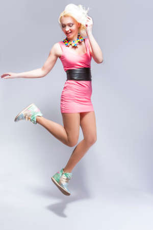 pinky: Fashion Concepts. Portrait of Smiling Sexy Caucasian Blond Female in Pink Short Dress and Sneakers. Posing In High jump Over White Background.