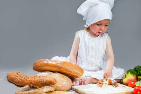 Cooking Ideas and Concepts. Portrait of Little Caucasian Girl in Cook Hat and Lips in Flour Sitting in Front of Fresh Buns and Fruits.Against Gray. Horizontal Image