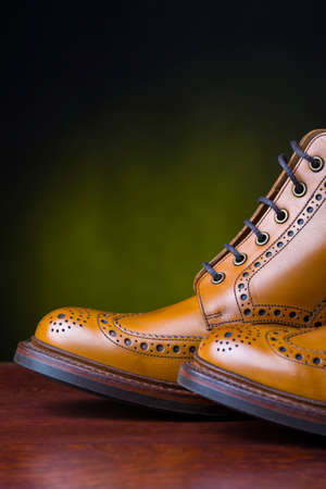 Footwear and Shoes Concepts. Pair of  Premium Tanned Brogue Derby Boots Made of Calf Leather with Rubber Sole. Shoot Against Dark Background.Vertical Image Stock Photo