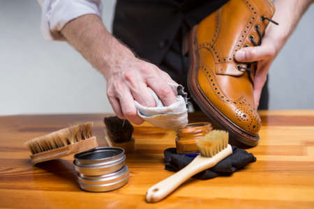 Footwear Concepts and Ideas. Closeup of Hands of Man Cleaning Premium Derby Boots With Variety of Brushes and Accessories.Horizontal Image Composition Banque d'images