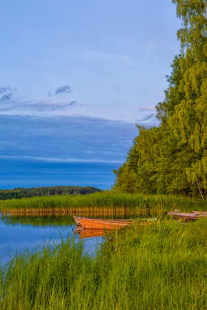 Travel Ideas and Concepts. Peaceful Picturesque Landscape of The Strusto Lake with Wooden Boats at Foreground. Lake is a Part of National Braslav Lakes Nature Reserve. Vertical Image