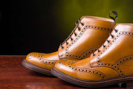 Footwear Concepts. Pair of  Premium Tanned Brogue Derby Boots Made of Calf Leather with Rubber Sole. Shoot Against Dark Background.Horizontal Image