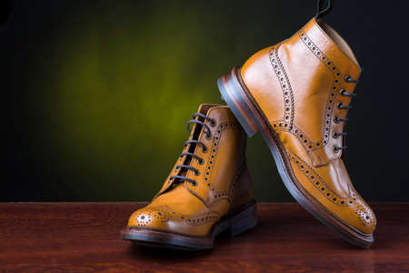 Footwear and Shoes Concepts. Pair of  Premium Tanned Brogue Derby Boots Shoot Against Dark Background.Horizontal Image Composition. Stock Photo