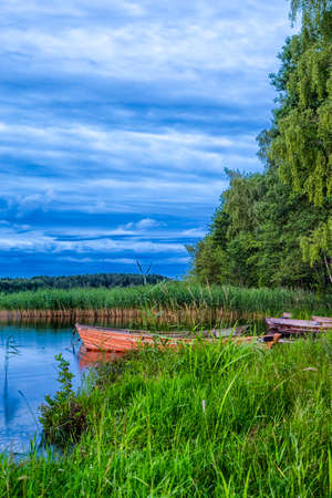 Travel Destinations Concepts. Peaceful Picturesque Landscape of The Strusto Lake with Wooden Boat at Foreground. Lake is a Part of National Braslav Lakes Reserve. Vertical Composition