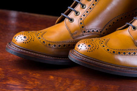 Footwear and Shoes Concepts. Pair of  Premium Tanned Brogue Derby Boots Made of Calf Leather with Rubber Sole. Shoot Against Dark Background.Horizontal Image Composition.