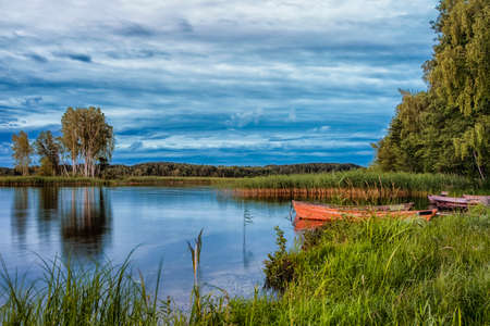 Travel Destinations Concepts. Peaceful Picturesque Landscape of The Strusto Lake with Wooden Boat at Foreground. Lake is a Part of National Braslav Lakes Reserve. Horizontal Composition