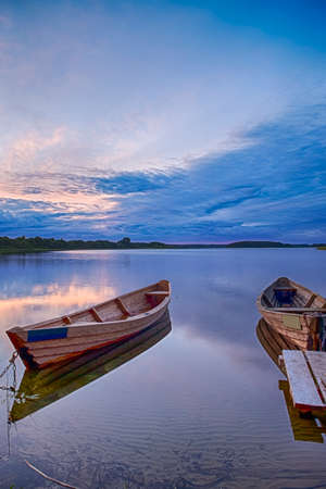Travel Destinations Concepts. Tranquil and Peaceful Picturesque Landscape of The Strusto Lake with Wooden Boats at Foreground. Lake is a Part of National Braslav Lakes Reserve. Vertical Image