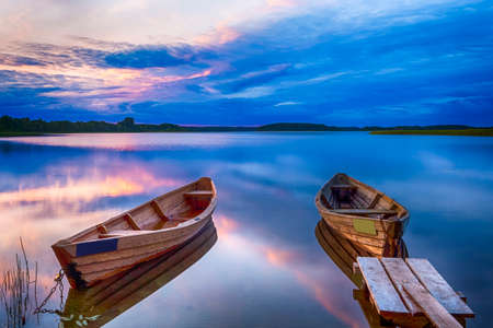 Travel Destinations Concepts. Tranquil and Peaceful Picturesque Landscape of The Strusto Lake with Wooden Boats at Foreground. Lake is a Part of National Braslav Lakes Reserve. Horizontal Image Stock Photo