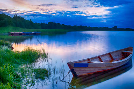 Travel Destinations Concepts. Tranquil and Peaceful Picturesque Landscape of The Strusto Lake with Wooden Boat at Foreground. Lake is a Part of National Braslav Lakes Reserve. Horizontal Image Composition Stock Photo