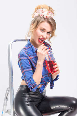 Portrait of Happy Smiling Caucasian Blond Woman in Black Latex Pants Posing On Ladder with Cup of Red Juice and Straw. Stock Photo