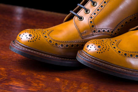 Pair of Premium Tanned Brogue Derby Boots Made of Calf Leather with Rubber Sole. Shoot Against Dark Background.Horizontal Image Orientation
