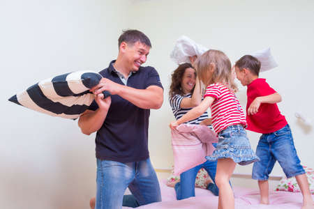 Family Concepts and Ideas. Young Caucasian Family of Four Having a Playful Funny Pillow Fight Indoors.Positive Emotional Expression. Horizontal Image
