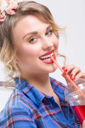 Portrait of Happy Smiling Caucasian Blond Woman in Checked Shirt Drinking Red Juice Using Straw. Against White.
