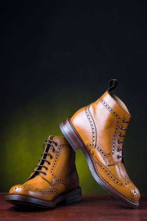 Footwear and Shoes Concepts. Pair of  Premium Tanned Brogue Derby Boots Shoot Against Dark Background.Vertical Image