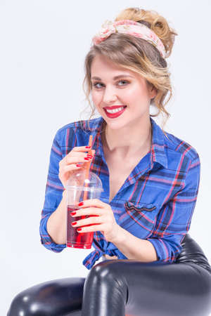 Portrait of Happy Smiling Caucasian Blond Woman in latex pants Posing with Cup of Red Juice and Straw. Against White.