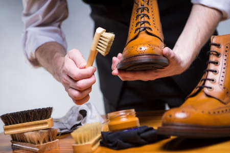 Footwear Ideas and Concepts. Extreme Close Up of Mans Hands Cleaning Luxury Calf Leather Brogues with Special Accessories, Shoe Wax and Tools. Horizontal Image Orientation