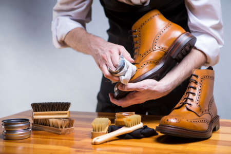 Footwear Ideas and Concepts. Extreme Close Up of Mans Hands Cleaning Luxury Calf Leather Brogues with Special Accessories, Shoe Wax and Tools. Horizontal Composition Stock Photo