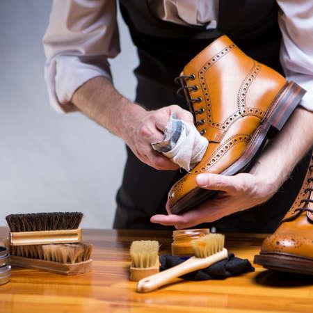 Idées et concepts de chaussures. Extrême gros plan des mains nettoyant des chaussures brogues de luxe en cuir de veau avec un chiffon spécial et de la cire pour chaussures. Orientation Carrée