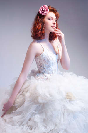 Wedding Concepts. Young Caucasian Red-Haired Female Wearing Tailored Wedding Dress.