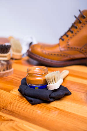 Footwear Concepts.Closeup of Premium Tan Brogue Boots Along with Cleaning Accessories and Cleaning Cloth.Vertical Image