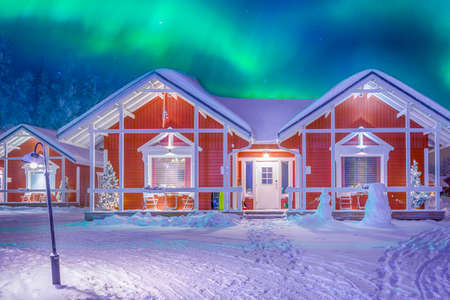 Travel Destinations Concepts. Beautiful Multicoloured Vibrant Aurora Borealis known as Northern Lights Playing with Vivid Colors Over Traditional Lapland Houses in Finland.Horizontal Orientation Фото со стока