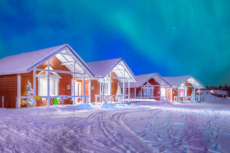 Travel Destinations Concepts. Beautiful Multicoloured Vibrant Aurora Borealis known as Northern Lights Playing with Vivid Colors Over Traditional Lapland Houses in Finland.Horizontal Image Composition Stock Photo