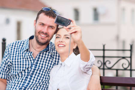Travel Ideas and Concepts. Young Caucasian Couple in Love Sitting on Bench Outdoors While Taking Selfie Pictures.Horizontal Image Orientation