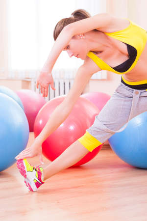 Sport, Fitness, Wellness and Lifestyle Ideas.Portrait of Female Caucasian Athlete In Good Fit Having Body Shape and Stretching Exercises. Posing Against Fitballs in Gym.Vertical Shot Stock Photo
